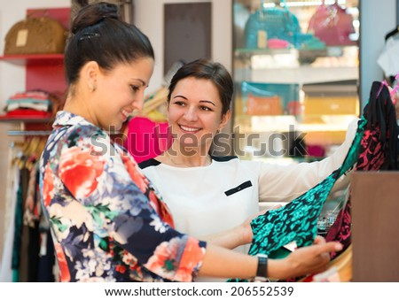 Two young women in clothes boutique choosing dress - stock photo