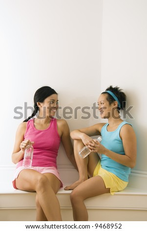 Two young women in fitness clothes holding water bottles sitting smiling and talking.