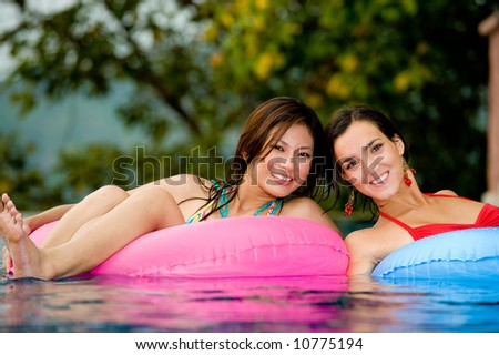 Two young women in inflatables in the pool - stock photo