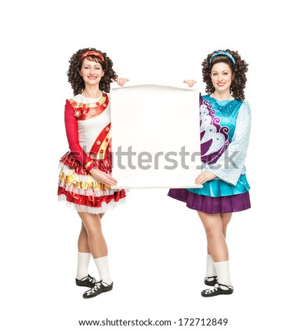 Two young women in irish dance dresses with empty paper - stock photo