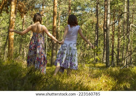 two young women in long dresses  holding each other's hand are roaming through the forest in springtime
