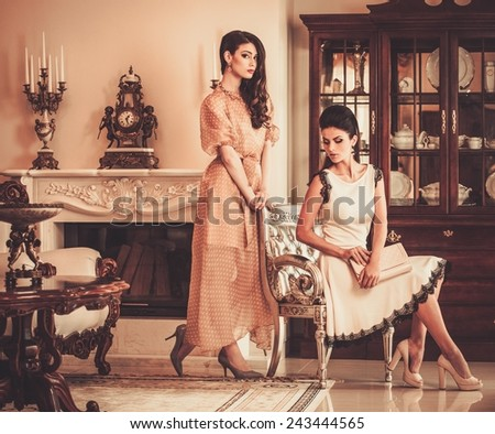 Two young women in luxury house interior  - stock photo