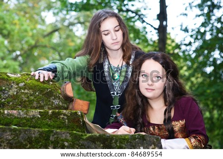 Two young women in medieval dresses writing papers