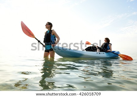 Two young women in ocean with a kayak - stock photo