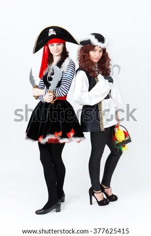 Two young women in pirate costumes on white background - stock photo
