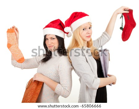 two young women in Santa hats with present bags and socks - stock photo