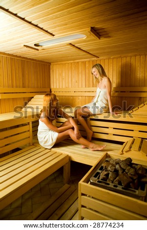 Two young women in sauna. They looks happy. - stock photo