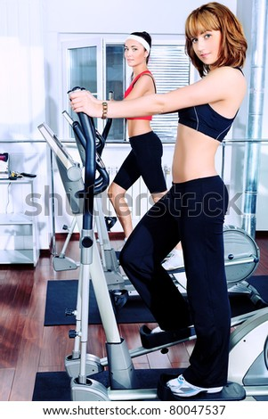 Two young women in the gym centre. - stock photo