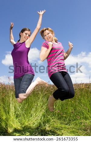 Two young women jumping around on a meadow - stock photo