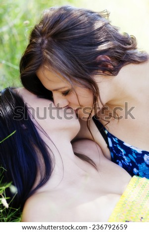 Two Young Women Kissing Each Other Outdoors