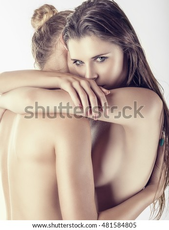 Two young women lesbians in each other's arms on a white background