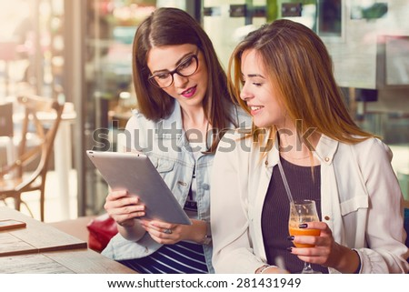 Two young women looking at a tablet - stock photo