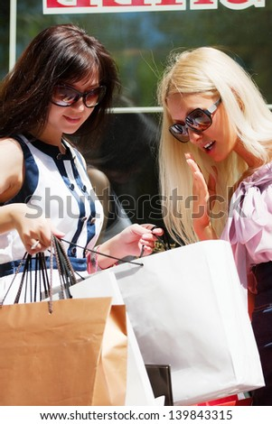 Two young women looking at shopping bags - stock photo