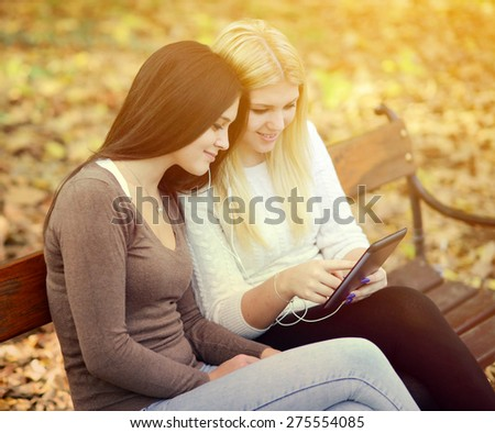 Two young women looking at tablet and chating online with friend - stock photo