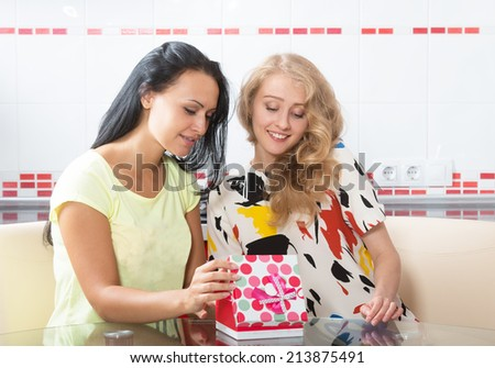 Two young women looking at the gift box - stock photo