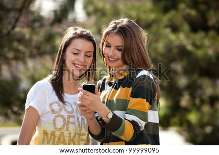 two young women looking at the phone - stock photo