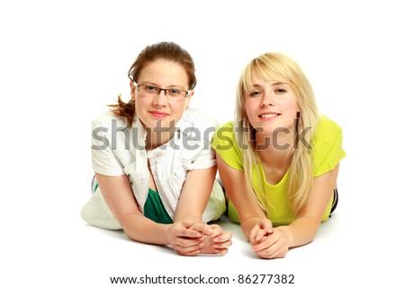 Two young women lying on floor isolated - stock photo