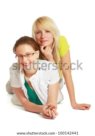 Two young women lying on floor isolated on white background