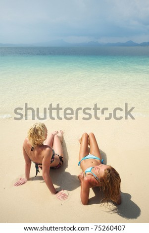 Two young women lying on sand and looking to a horizon - stock photo