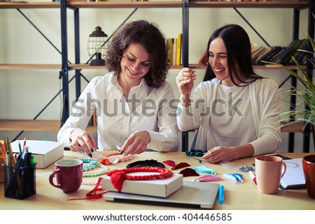 Two young women making handmade jewelry and laughing