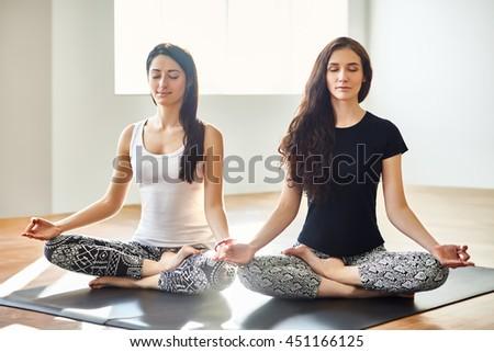 Two young women meditating in Lotus Pose. Padmasan - stock photo