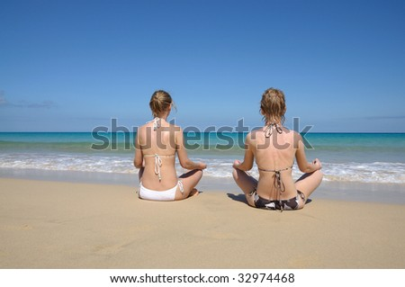 Two young women meditating on the tropical beach. Fuerteventura, Canary Islands, Spain