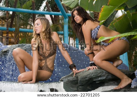 two young women near the swimming pool on resort - stock photo