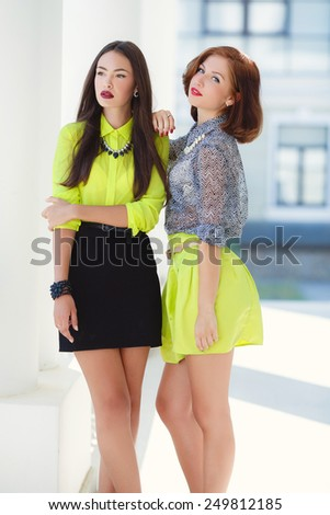 Two young women on a street. Two smiling fashion girls in the city. Two cheerful girls twins, in the street - stock photo