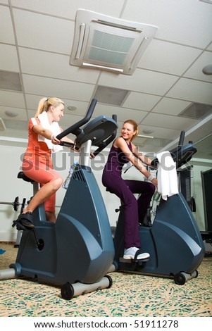 Two young women on exercise bikes in a gym. Vertical shot. - stock photo