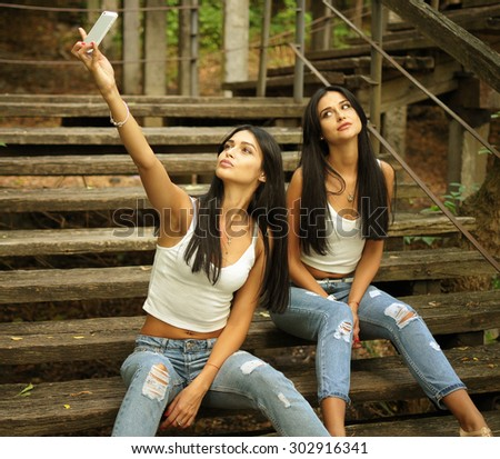 Two young women on the wooden stairs making selfie with smart phone - stock photo