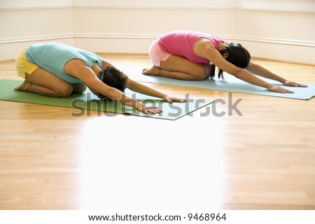 Two young women on yoga mats doing child's pose. - stock photo