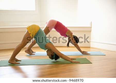Two young women on yoga mats doing downward facing dog pose. - stock photo
