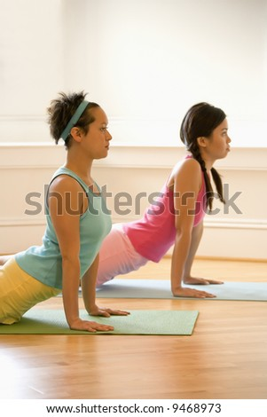 Two young women on yoga mats doing upward cobra pose. - stock photo
