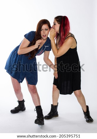 Two young women, one with red hair and one with dyed red hair, share a secret.