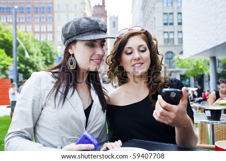 two young women outside at a cafe reading text message - stock photo