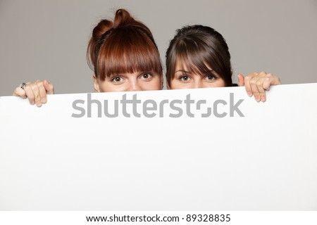 Two young women peeking over edge of blank empty paper billboard with copy space for text, over grey background - stock photo