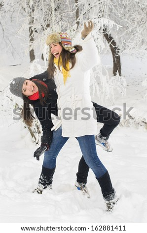Two young women playing in the snow - stock photo