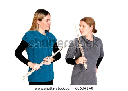 Two young women playing transverse flute, isolated on white background. - stock photo
