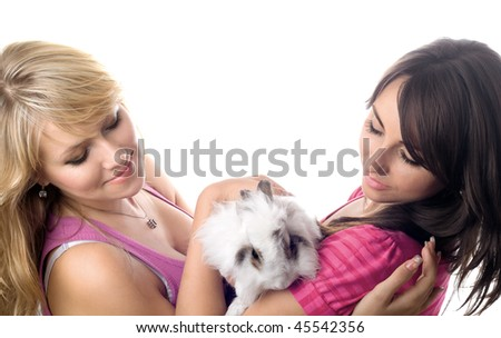 Two young women playing with little rabbit. Isolated on white