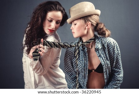 Two young women portrait. On dark wall background.