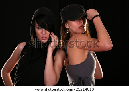 Two young women posing on black background - stock photo