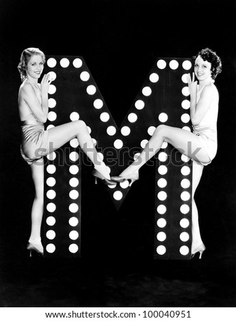 Two young women posing with the letter M - stock photo