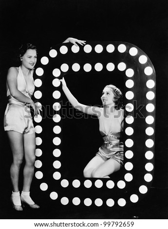 Two young women posing with the letter O - stock photo