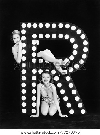 Two young women posing with the letter R - stock photo