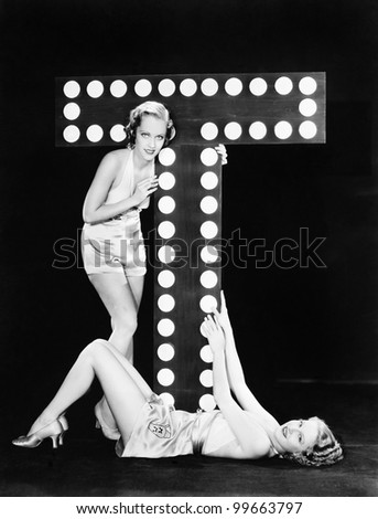 Two young women posing with the letter T