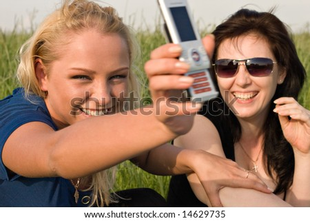 Two young women reading sms message on mobile phone