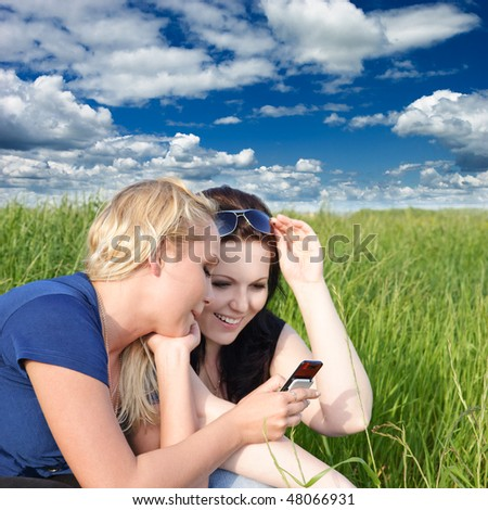 Two young women reading sms message on mobile phone - stock photo