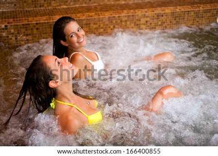 Two young women relaxing in a jacuzzi - stock photo