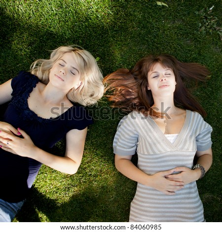 Two young women relaxing on grass - stock photo