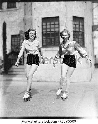 Two young women roller skating on the road and smiling - stock photo